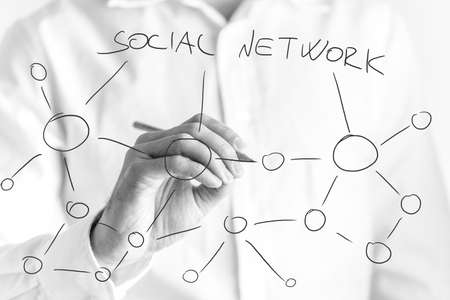 interconnected: Man drawing a social network of contacts with a black marker on a virtual interface with a series of hubs interconnected by links Stock Photo