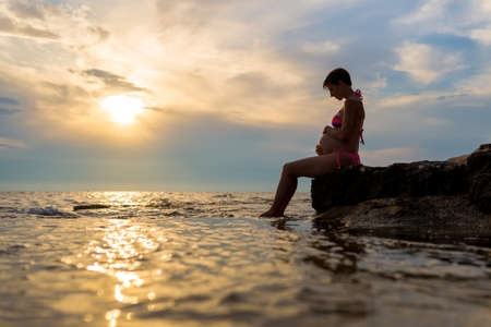 cradling: Pregnant woman in a swimsuit sitting in profile cradling her swollen belly on a rock by the sea at sunset