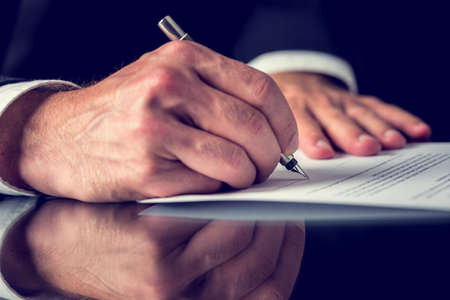 to document: Closeup of male hand signing mortgage or other important legal or business document. Stock Photo