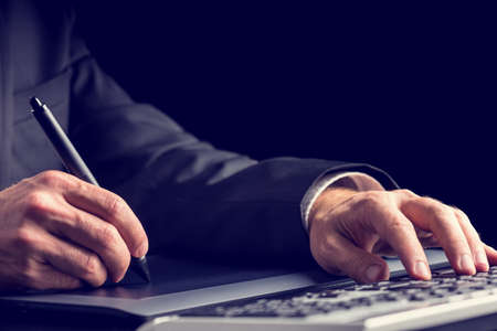 simultaneously: Businessman typing on a computer keyboard while simultaneously using a tablet and stylus Stock Photo