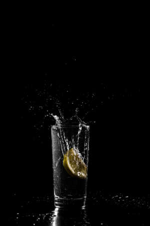 tangy: Wedge of fresh tangy lemon dropping into a cold drink of water or alcohol in a tall glass with a splash and spray of droplets against a dark background