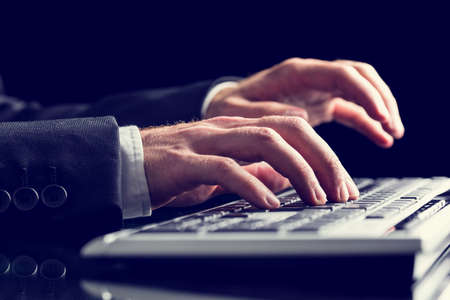 Retro image of businessman hands using office computer keyboard photo