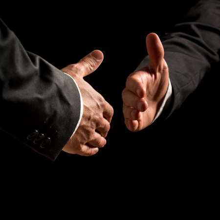 shadowy: Hands of two businessmen reaching out in a business handshake with receding perspective on a dark shadowy background conceptual of a deal, partnership, agreement, congratulations or greeting.