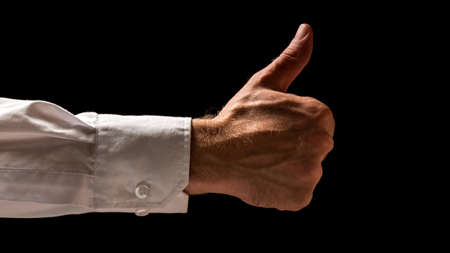 shadowy: Dark shadowy image of the arm and hand a businessman in shirt sleeves giving a thumbs up gesture of success, approval and support.