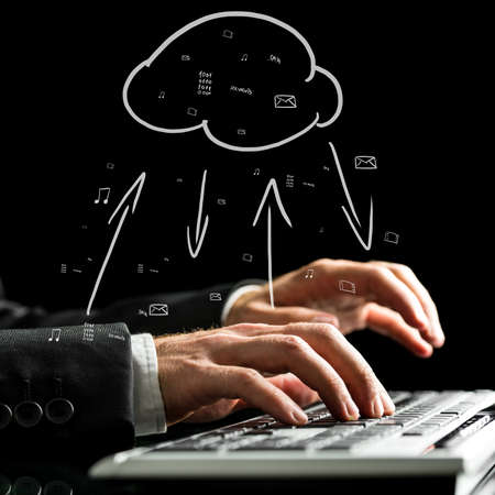 synchronizing: Businessman typing on the keyboard of his computer synchronizing files with the cloud storage with a hand-drawn cloud icon with data transfer arrows. Stock Photo