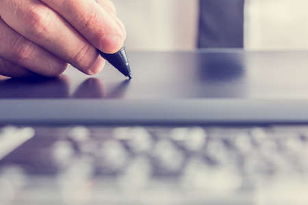 Retro image of male hand of a designer drawing with the stylus on a grey graphics tablet, close-up.