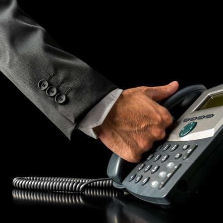 clavados: Primer plano de la mano de un hombre de negocios levantar el auricular de un teléfono de línea terrestre negro, colocado sobre el escritorio, con copia espacio en negro Foto de archivo