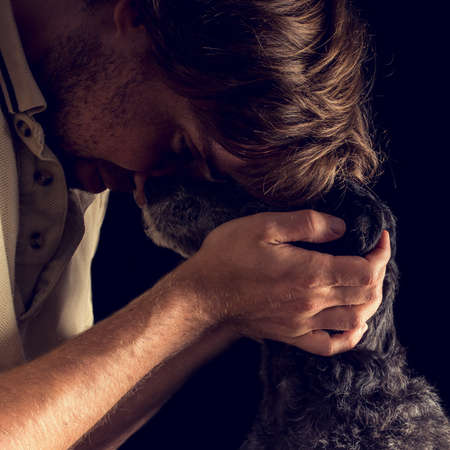 tenderly: Retro image of loving man hugging his terrier resting his forehead on the dogs face as he tenderly cups its head with both hands, profile view. Stock Photo