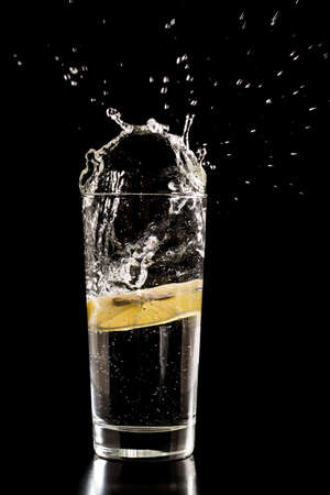 energizing: Slice of lemon splashing into a glass of water with a spray of water droplets in motion suspended in the air above the glass on a dark background.