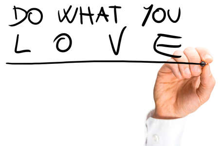 urging: Male hand writing on a virtual transparent screen an inspirational message urging to do what you love, with copy space on white.