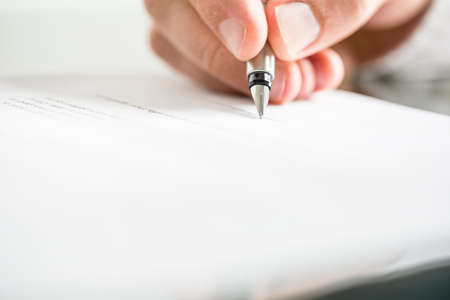contratos: Ángulo de visión baja de los dedos de un hombre escribiendo en un documento con una pluma estilográfica conceptual de la comunicación, correspondencia, acuerdo comercial, contrato legal o la creatividad. Foto de archivo