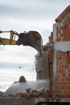 unauthorized: Bucket of a backhoe or mechanical digger against the skyline demolishing the wall of a brick building with flying masonry and debris. Stock Photo