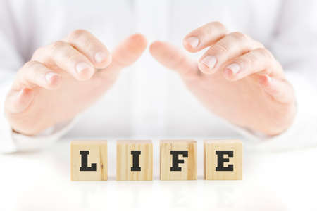 Nurturing hands of a man cupped protectively over the word Life on four wooden blocks, spiritual inspirational conceptual image. photo