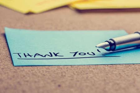 Handgeschreven bedankbriefje geschreven op een blauwe kleverige nota liggend op een kurk boord met een vulpen bekeken lage hoek. Stockfoto