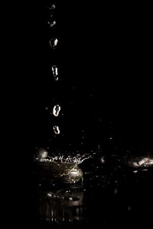 liquid reflect: Glistening silvery pure fresh water droplets splashing onto a reflective black surface in a spray of liquid on a dark background with copyspace.