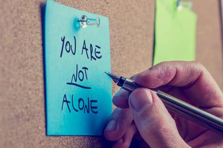 alone: Usted no está solo - hombre que escribe un mensaje de inspiración en una nota adhesiva azul clavada en un tablero de corcho con una pluma estilográfica.