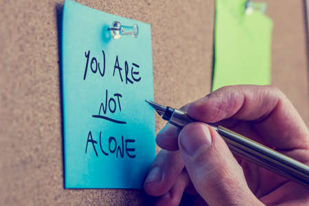 helping: You Are Not Alone - man writing an inspirational message on a blue sticky note pinned to a cork board with a fountain pen.