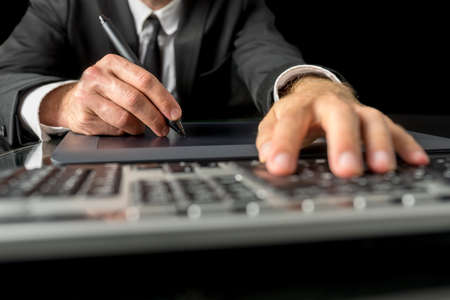 navigate: Close up view of the hands of a businessman, photographer, graphic designer or illustrator using a tablet and stylus, to navigate on a desktop computer and to do processing and drawing.