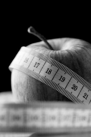 centimetres: Tape measure wound around an apple in a black and white diet, health, weight loss and fitness concept with copyspace on a black background. Stock Photo