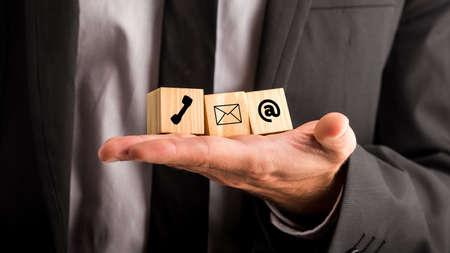 電話、メール、連絡先、アドバイス、チャットやサポートをメールを描いた彼の手で 3 つの木製のブロックを保持している実業家と通信概念。