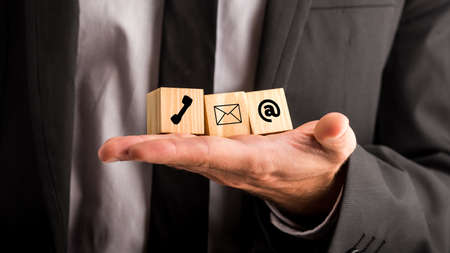 contact person: Communications concept with a businessman holding three wooden blocks in his hand depicting a telephone, mail and email for contact, advice , chat and support. Stock Photo
