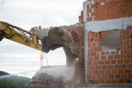 View of the hydraulic arm and bucket of a large heavy duty backhoe demolishing a brick house breaking down the exterior wall for removal. photo