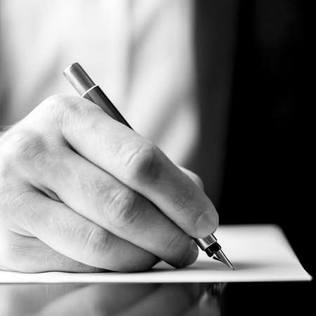 Low angle black and white image of a male hand holding a fountain pen as though writing on a blank sheet of paper with shallow dof in square format.