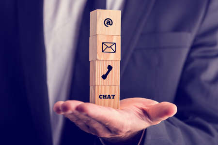 Online business communications concept with a businessman holding a stack of four wooden cubes balanced on his palm displaying icons for email, a web address, mail, telephone and chat.