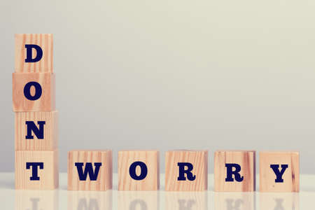 dont worry: The inspirational words - Dont Worry - on wooden blocks arrange vertically and horizontally in the bottom left corner with copyspace for your motivational message.