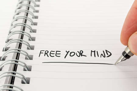 free your mind: Close-Up of Hand with Pen Writing in Black Ink Free Your Mind in Spiral Bound Notebook.