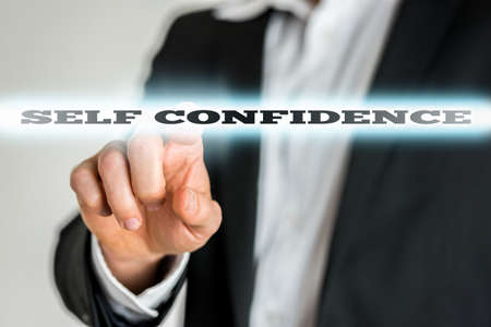 self confidence: Closeup of businessman activating a Self confidence button on virtual screen. Stock Photo