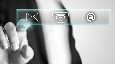 Hombre mano presionando con el dedo sobre el icono de correo de una sección de contacto aparece en una pantalla interactiva.