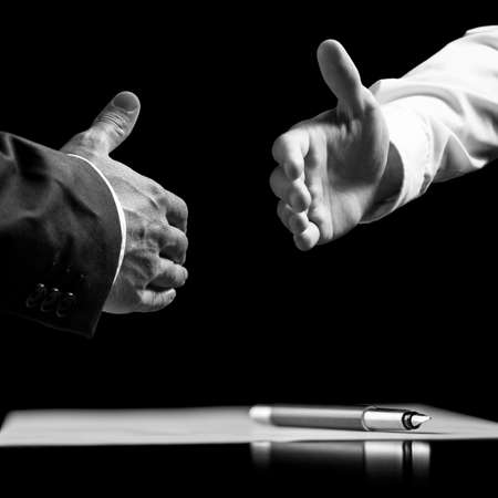 Monochrome image of two businessmen about to shake hands over a signed contract. Stock Photo