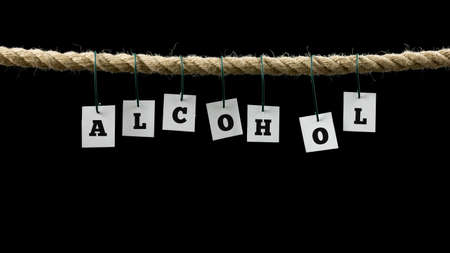 abusing: White tags with black capital letters forming the word alcohol, hanging on a rope, with copy space on black. Stock Photo