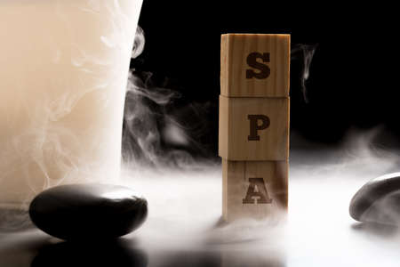 basalt: Spa concept with the word spa in alphabet letters on stacked wooden cubes with massage stones in swirling steam or mist conceptual of a hot stone massage treatment. Stock Photo