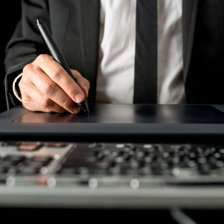 low angle views: Hombre de negocios usando una tableta y l�piz para navegar en su computadora de escritorio, de cerca vista de �ngulo bajo de la mano por el teclado del ordenador.