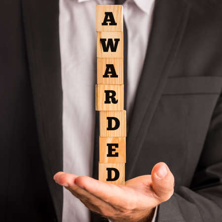 awarded: Businessman holding a stack of blocks in the palm of his hand with the words Awarded. Stock Photo