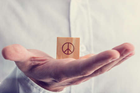 anti war: Man holding a wooden block with the peace sign balanced on the palm of his hand in a conceptual image with a retro vintage filter effect.