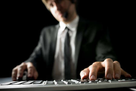 Man typing on a desktop computer keyboard with holding a mouse in his other hand, low angle view across the keyboard of a man in a suit with blurred features. photo