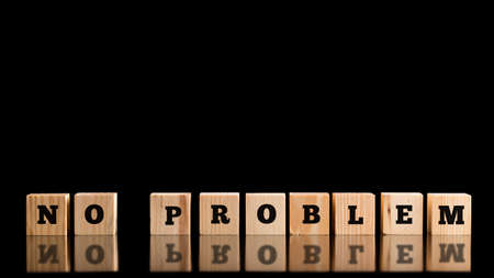 No Problem in alphabet letters on a row of wooden blocks on a dark reflective surface over a black background, conceptual image. photo