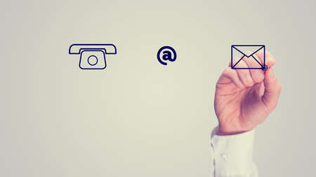 One Hand Making Web Graphic Elements of Phone, At Sign and Envelope, Isolated on Gray Sky Background.