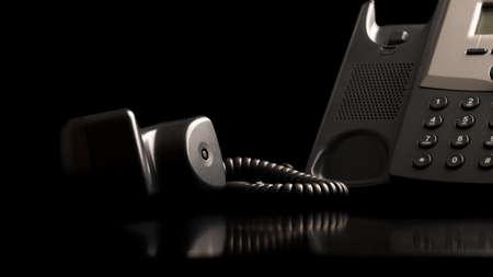 Telefoon hoorn van de haak liggend op een zwarte reflecterend oppervlak naast het instrument, close-up lage hoek weergave met copyspace.