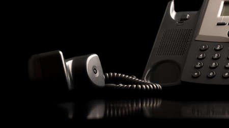 Telephone handset off the hook lying on a black reflective surface alongside the instrument , close up low angle view with copyspace. photo