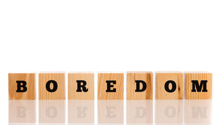 disinterested: The word - Boredom- on wooden cubes arranged in a line on a reflective white surface with copyspace above.