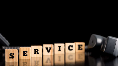The word Service on wooden blocks in a staggered receding line on a black reflective surface with copyspace and a telephone handset.