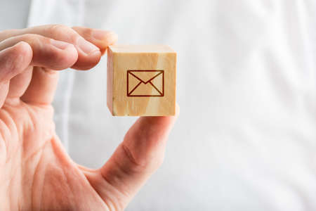 inbox: Male hand holding a wooden block with an envelope icon, creative symbol of contact, communication and electronic mail.