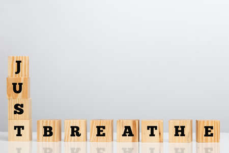 inhale: Wooden blocks spelling - Just Breathe - forming a corner border bottom left with its inspirational message, large copyspace for your text.