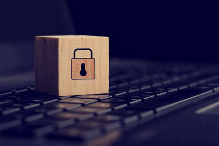 Close Up of Block with Lock Graphic on Black Computer Keyboard in Security Themed Image.