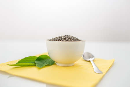 dietary fiber: Bowl of healthy dried chia seeds from the Salvia hispanica plant rich in omega-3 fatty acids, dietary fiber and protein with fresh green leaves on a place mat, copyspace above. Stock Photo