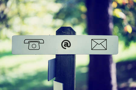 Computer Contact Icons Sign Affixed to Wooden Outdoor Signpost. Stock Photo